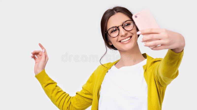 Mujer europea en la ropa casual que toma el autorretrato sobre la pared blanca del estudio Hembra feliz que toma un selfie en su  imagenes de archivo