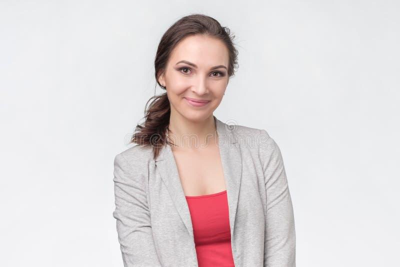 Mujer europea feliz en camisa roja y el traje que miran y que sonríen fotos de archivo