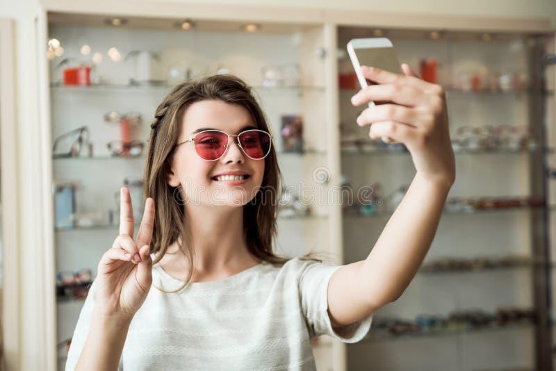 Mujer europea femenina apuesta en la tienda del óptico que toma el selfie mientras que intenta en las gafas de sol elegantes que  imágenes de archivo libres de regalías