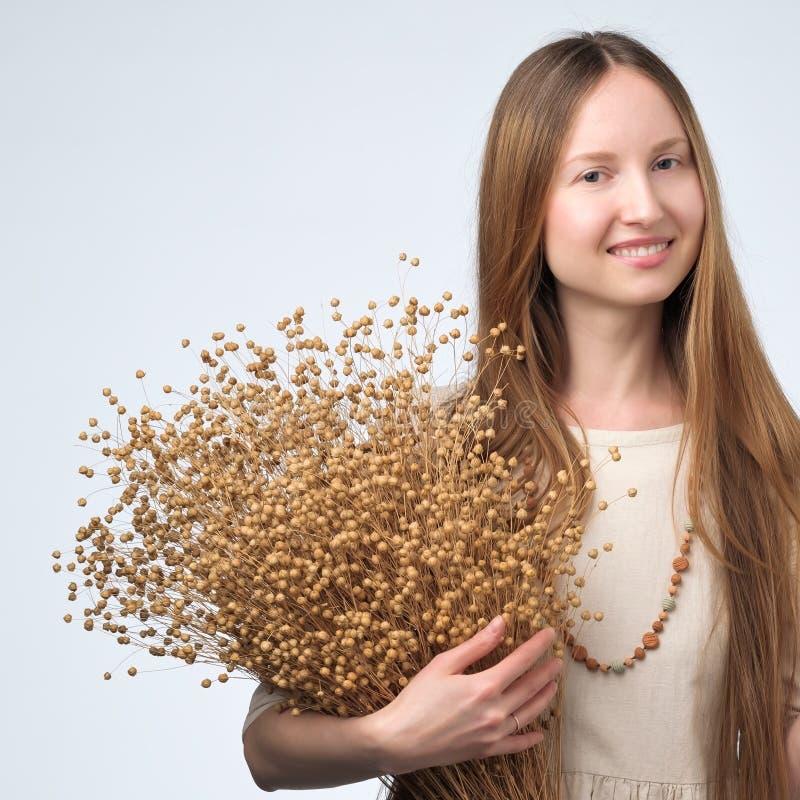 Mujer europea hermosa con el ramo largo de la tenencia del pelo de flores secas del lino fotos de archivo