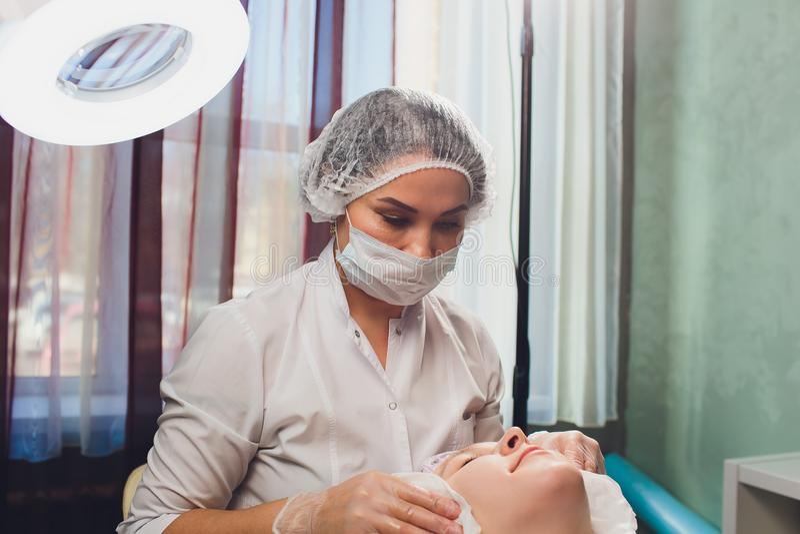 Mujer europea hermosa que tiene procedimiento facial de la piel aplicando una m?scara blanca del rejuvenecimiento del cosmetologi fotografía de archivo libre de regalías