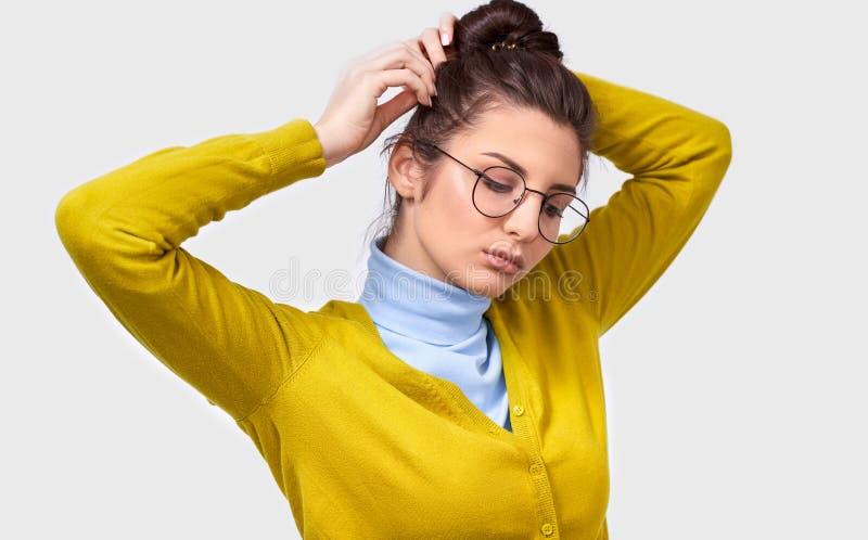 Mujer europea joven con la piel limpia sana, ropa casual que lleva, haciendo un peinado del nudo, con la expresión seria fotos de archivo libres de regalías