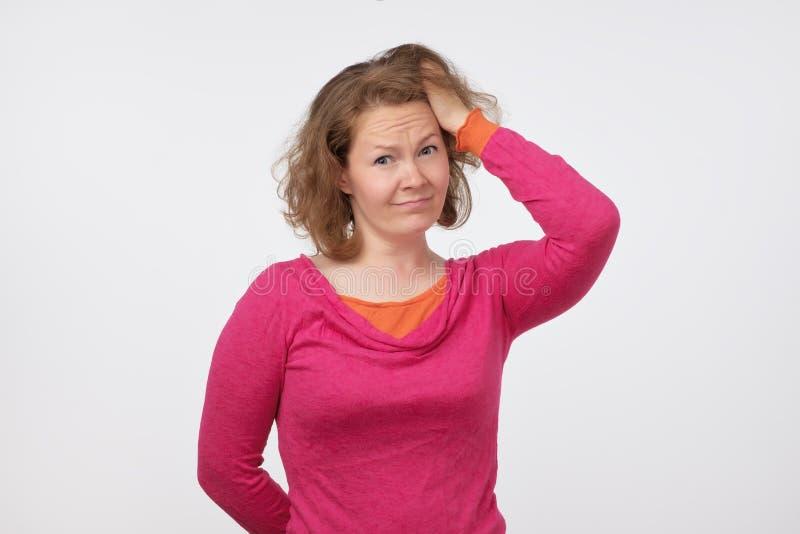 Mujer europea joven en el suéter rosado que mira con duda in camera Ella es confusa y no confía en las noticias fotos de archivo libres de regalías
