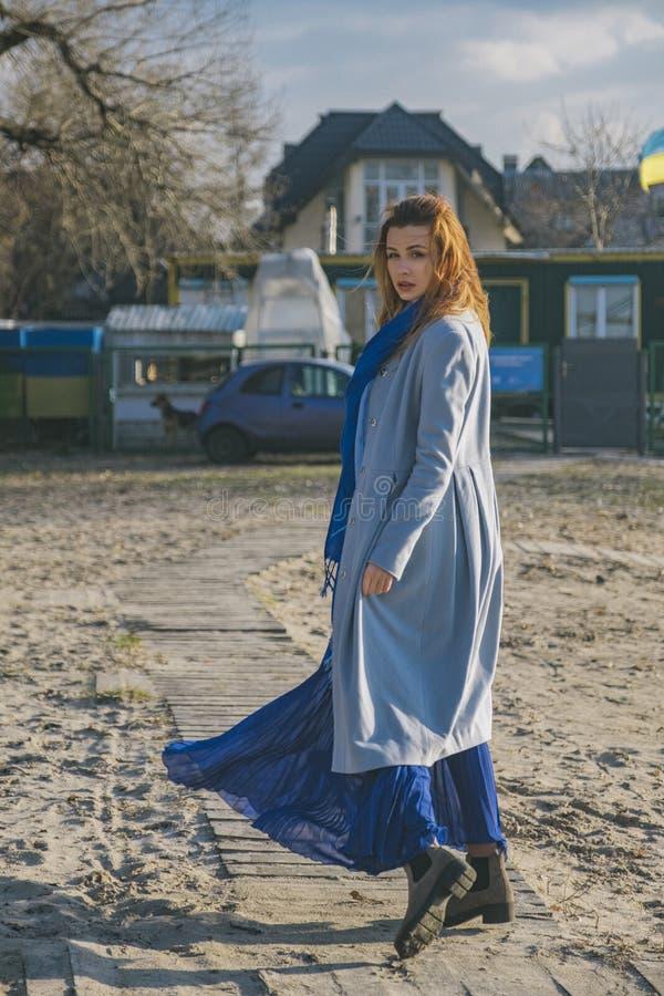 Mujer europea magnífica en capa y vestido calientes en un paseo en parque cerca del río Tiempo ventoso Su ropa vuela en el viento imagen de archivo