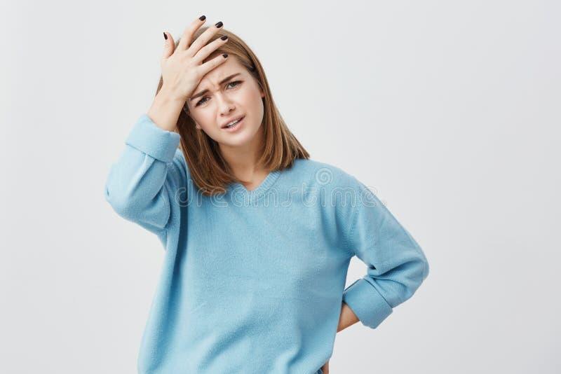 Mujer europea preocupante que la cierra ojos que llevan a cabo la mano en principal teniendo dolor de cabeza después de noche ins imagenes de archivo
