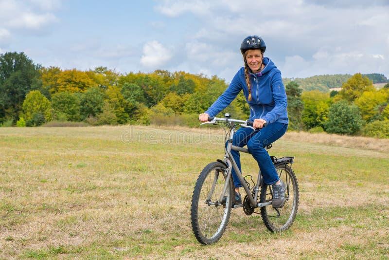 Mujer europea que completa un ciclo en la bici de montaña en naturaleza imagen de archivo libre de regalías
