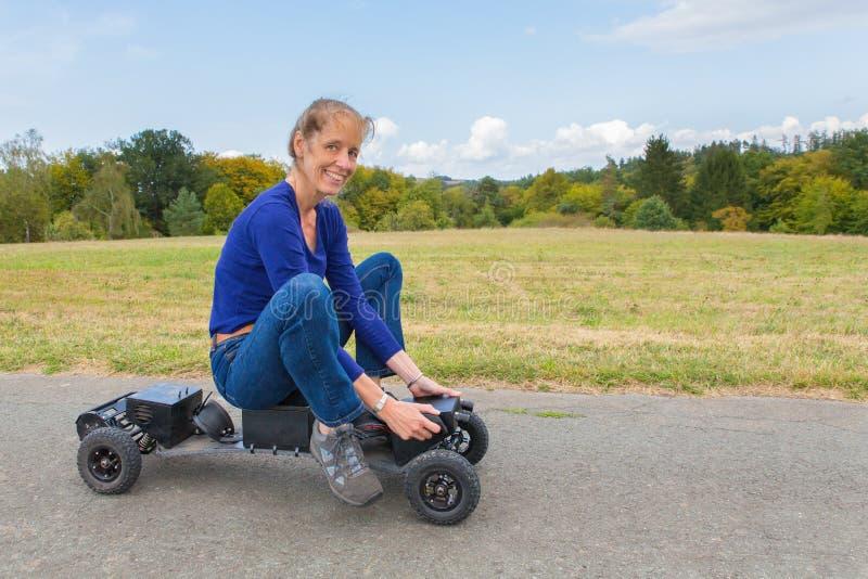 Mujer europea que conduce mountainboard eléctrico en naturaleza imagen de archivo libre de regalías