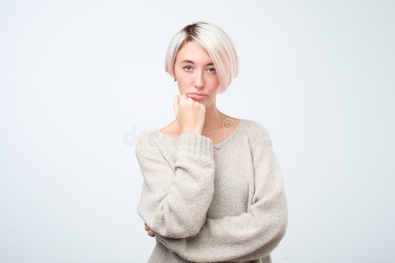 Mujer europea seria en el suéter gris que se coloca con los brazos cruzados foto de archivo