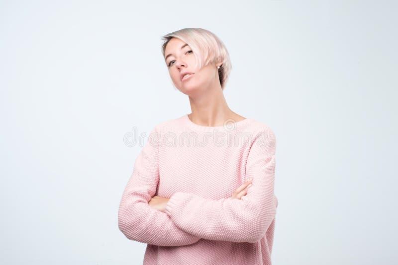 Mujer europea seria en el suéter rosado que se coloca con los brazos cruzados imagen de archivo libre de regalías