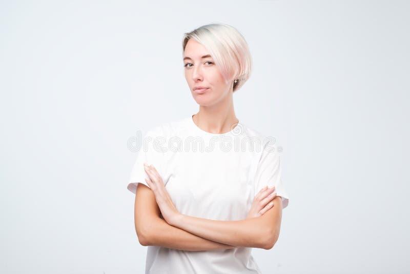 Mujer europea seria en la camiseta blanca que se coloca con los brazos cruzados imagen de archivo