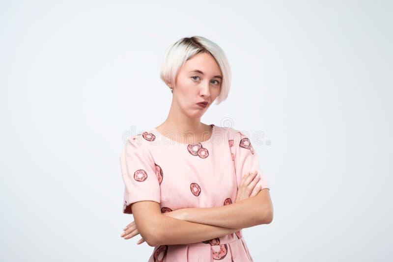 Mujer europea seria en los sdress rosados que se colocan con los brazos cruzados fotos de archivo