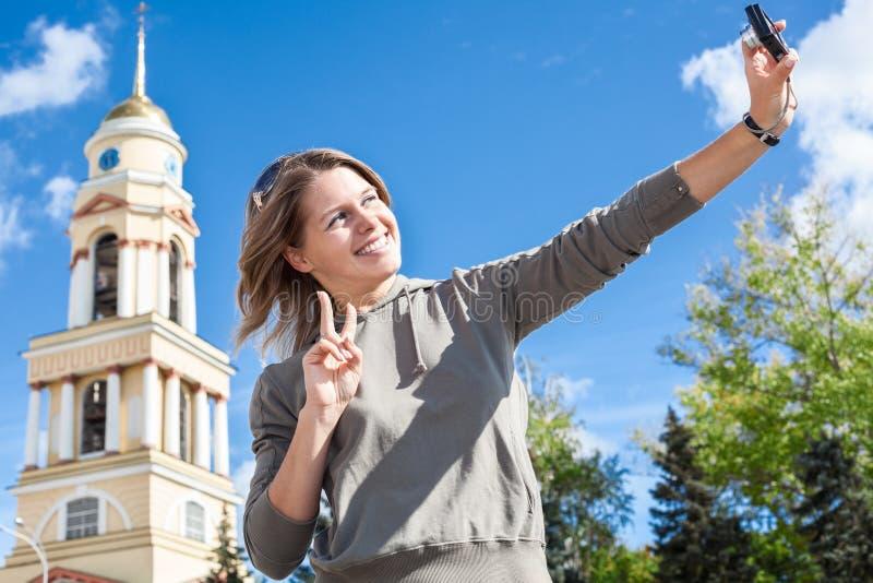 Mujer europea sonriente de los jóvenes que toma la imagen del autorretrato con la cámara fácilmente manejada contra el campanario imagenes de archivo