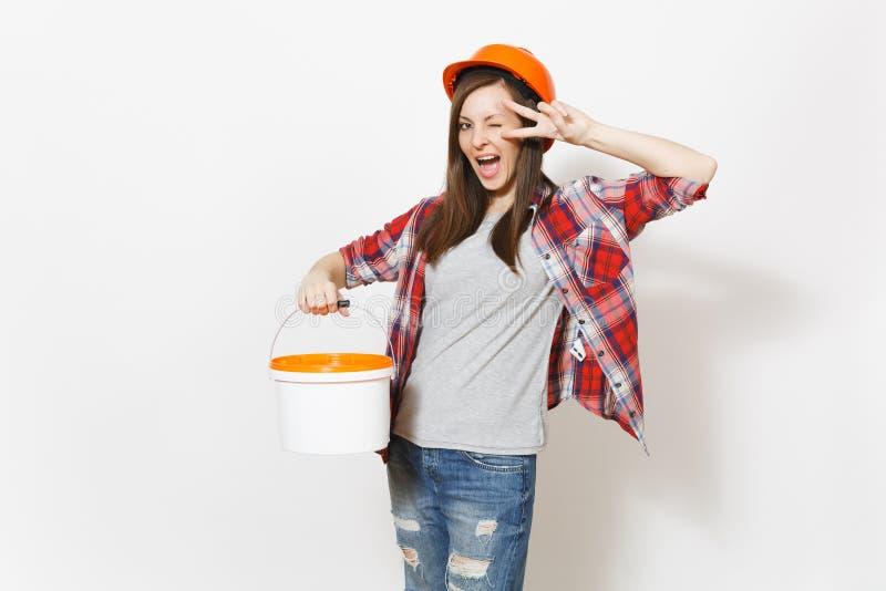 Mujer extática en el casco de protección protector que sostiene el cubo vacío de la pintura con el espacio de la copia y que mues foto de archivo libre de regalías