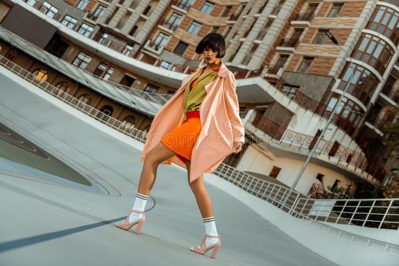 Mujer extraordinaria colorida del chocolate que camina extensamente en zapatos rosados imagenes de archivo