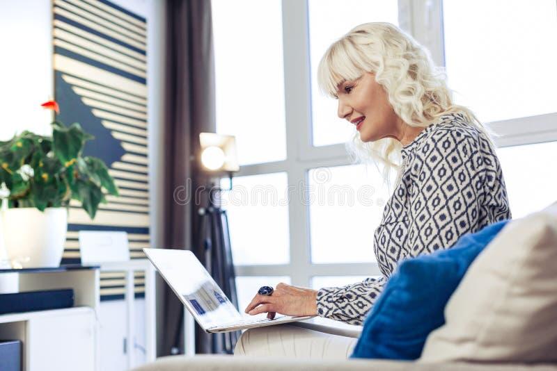 Mujer feliz agradable que mira la pantalla del ordenador portátil imagenes de archivo