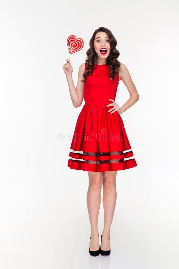 Mujer feliz alegre en el vestido rojo que sostiene la piruleta en forma de corazón imagen de archivo