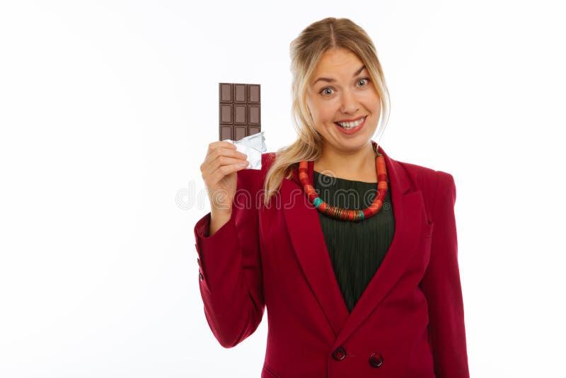 Mujer feliz alegre que le muestra el chocolate con leche fotografía de archivo libre de regalías