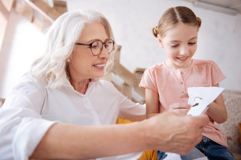 Mujer feliz alegre que mira su bordado de las nietas imagenes de archivo