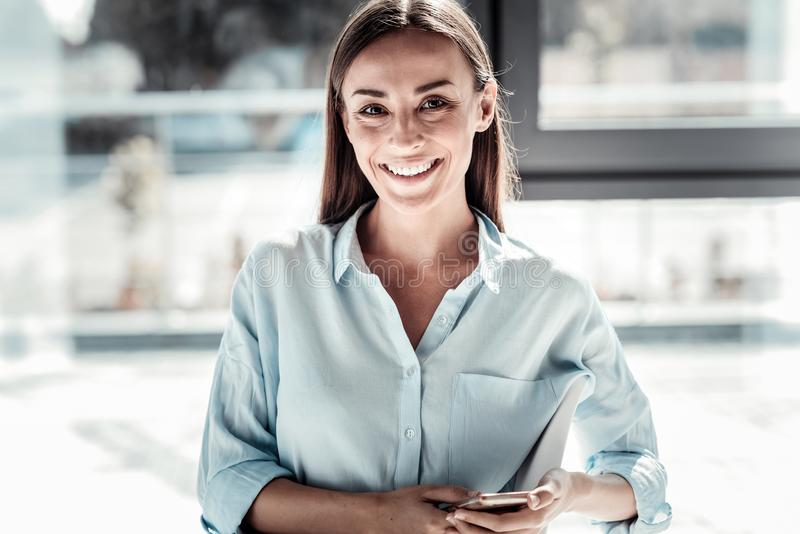 Mujer feliz alegre que sostiene su smartphone fotografía de archivo libre de regalías