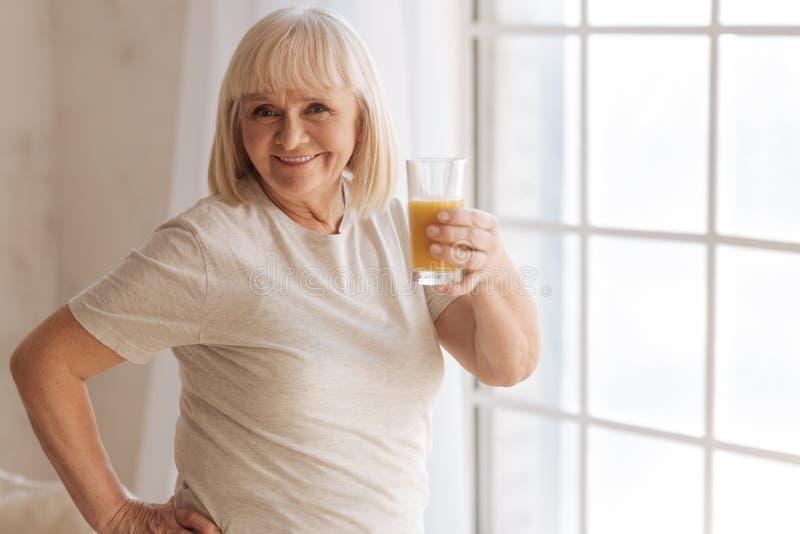 Mujer feliz alegre que sostiene un vidrio con el zumo de naranja foto de archivo