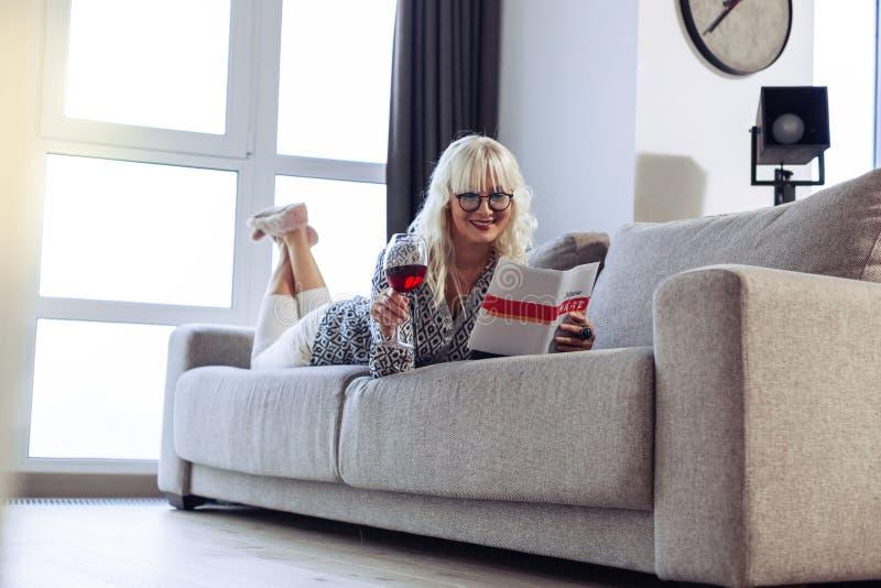 Mujer feliz alegre que sostiene una copa de vino fotografía de archivo libre de regalías