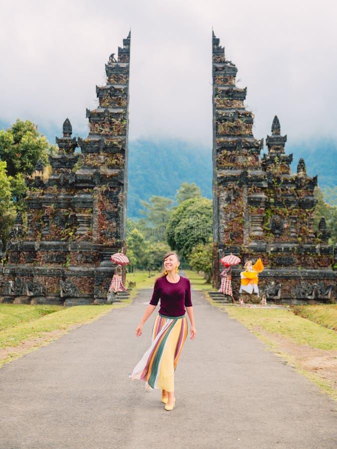 Mujer feliz atractiva con arquitectura del Balinese de la tradición en Bali foto de archivo