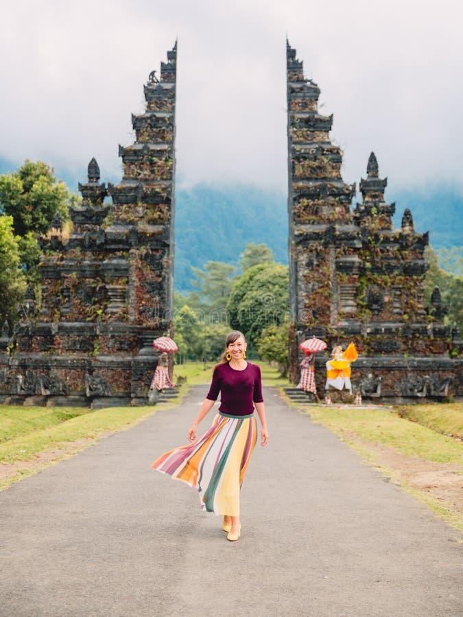Mujer feliz atractiva en vestido con arquitectura del Balinese de la tradición en Bali imagen de archivo libre de regalías