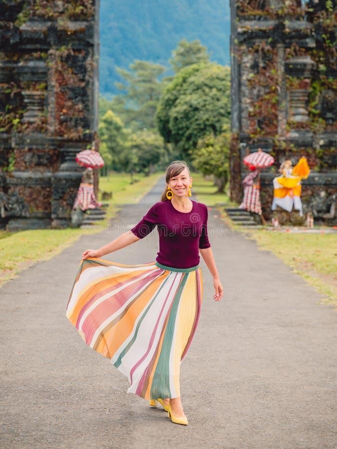 Mujer feliz atractiva en vestido y arquitectura del Balinese de la tradición en Bali imagen de archivo