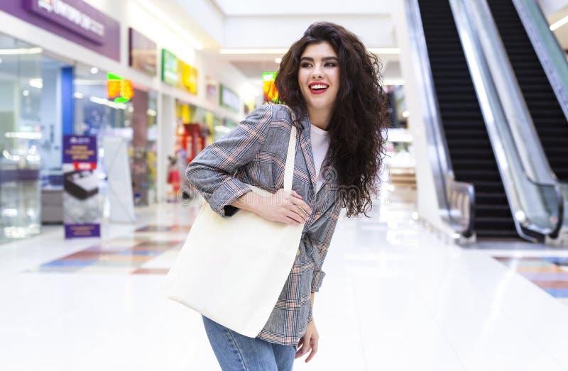Mujer feliz con compras de bolsos ecológicos en blanco en el centro comercial de la ciudad fotografía de archivo