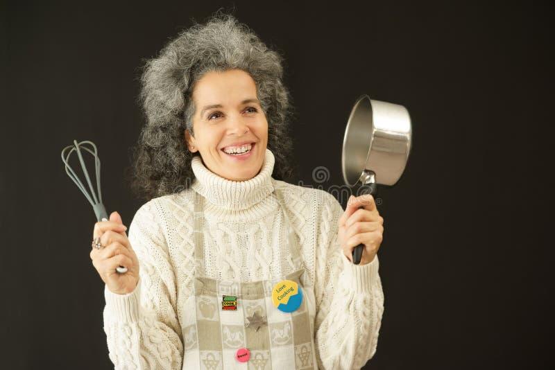 Mujer feliz con el delantal, el wisk y el cazo fotos de archivo
