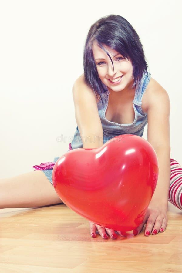 Mujer feliz con el globo del corazón imagenes de archivo