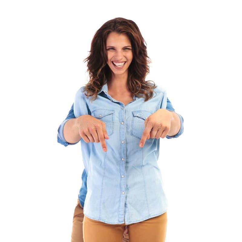 Mujer feliz con el hombre detrás de ella que señala abajo foto de archivo libre de regalías