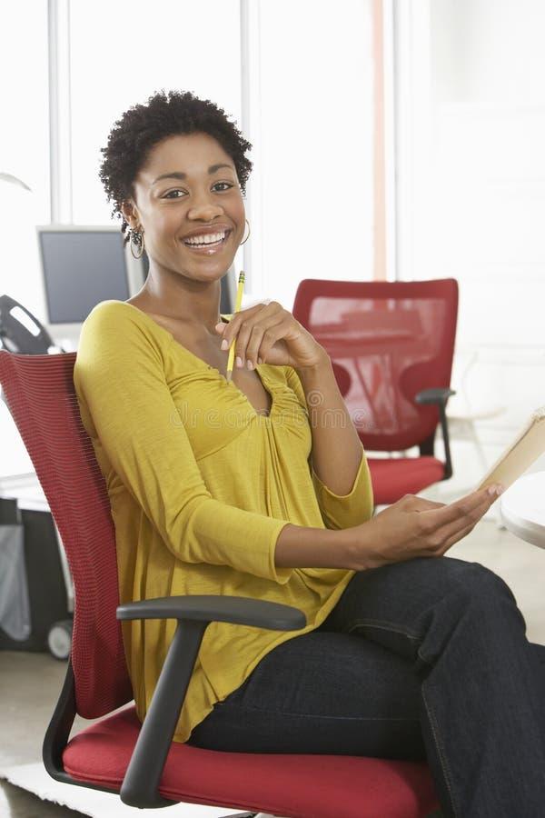 Mujer feliz con el lápiz y la libreta que se sientan en silla de la oficina imagenes de archivo