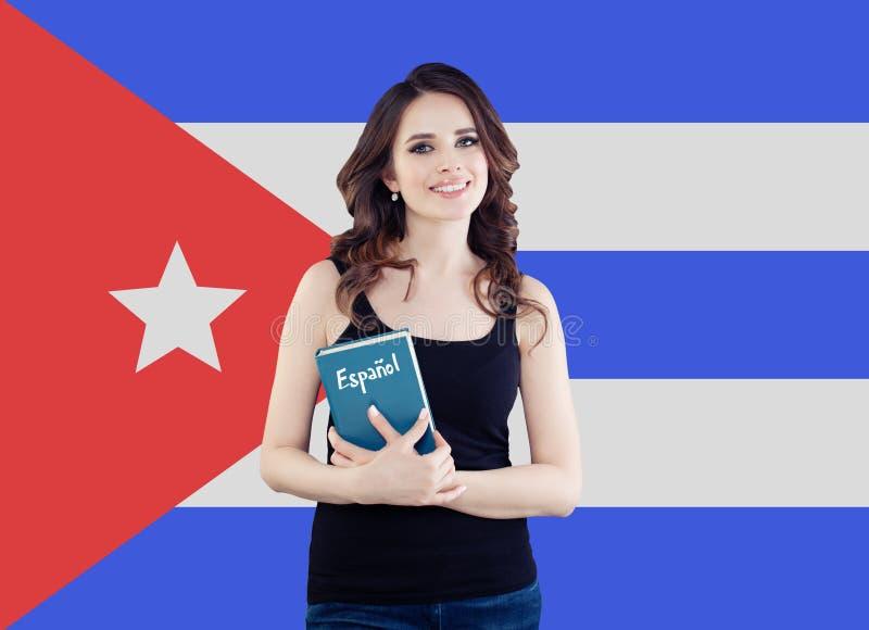 Mujer feliz con el libro contra el fondo de la bandera de Cuba Aprenda la lengua española imagenes de archivo