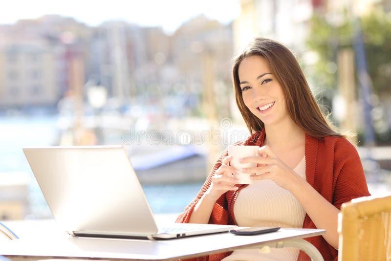 Mujer feliz con el ordenador portátil que le mira en una barra imagenes de archivo