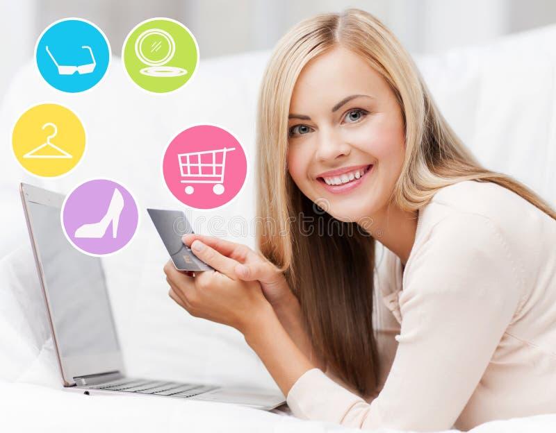 Mujer feliz con el ordenador portátil y compras de la tarjeta de crédito imagen de archivo