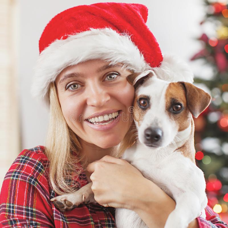 Mujer feliz con el perro en la decoración de la Navidad foto de archivo