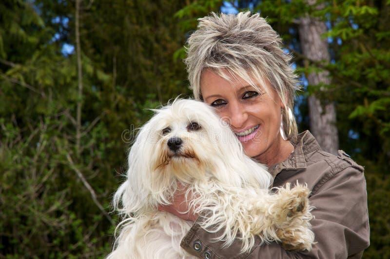 Mujer feliz con el perro largo del pelo fotografía de archivo libre de regalías