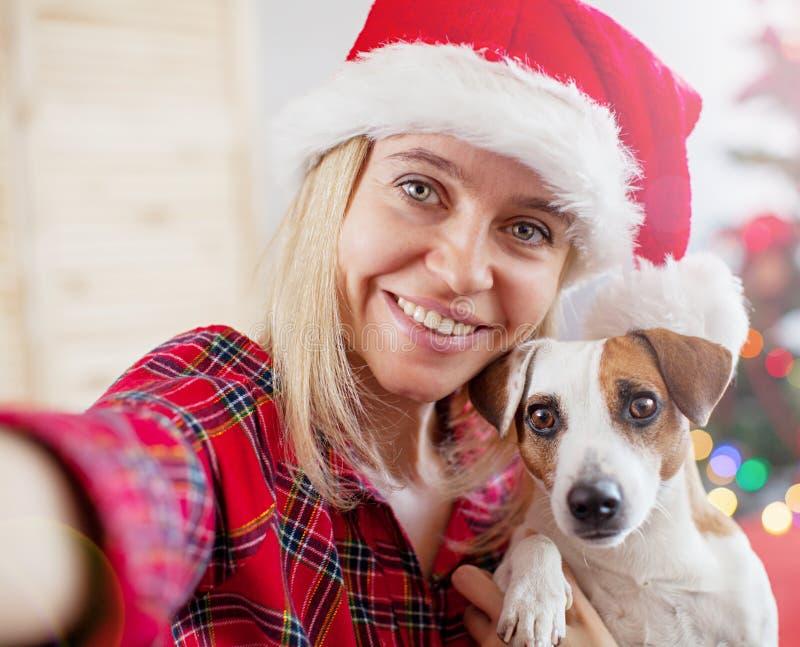 Mujer feliz con el perro tomar un selfie en la decoración de la Navidad imágenes de archivo libres de regalías