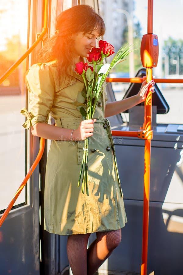 Mujer feliz con el ramo color de rosa en tranvía imágenes de archivo libres de regalías