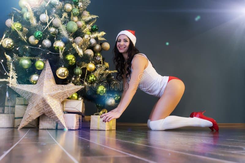 Mujer feliz con el regalo debajo del árbol de navidad La muchacha hermosa atractiva joven en ropa interior y el casquillo de Sant foto de archivo libre de regalías