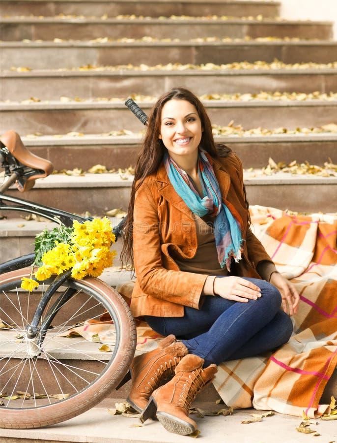 Mujer feliz con la bici en parque del otoño foto de archivo