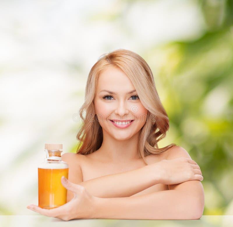 Mujer feliz con la botella de aceite foto de archivo