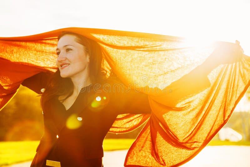 Mujer feliz con la bufanda que agita marrón larga en puesta del sol fotos de archivo