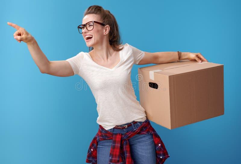 Mujer feliz con la caja de cartón que señala en algo en azul fotografía de archivo