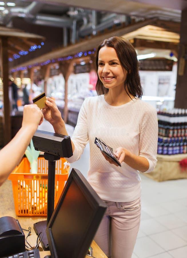 Mujer feliz con la comida de compra de la tarjeta de crédito en mercado fotografía de archivo libre de regalías
