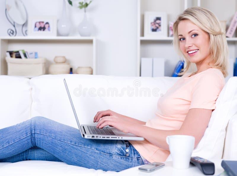 Mujer feliz con la computadora portátil foto de archivo