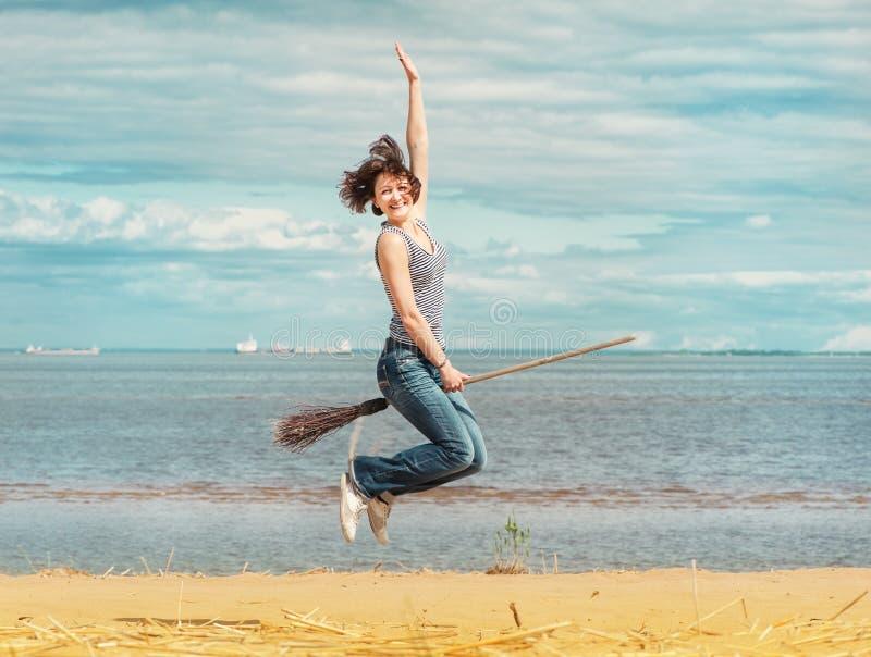 Mujer feliz con la escoba que salta en la playa fotos de archivo libres de regalías