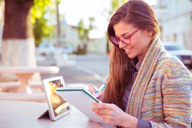 Mujer feliz con la escritura del lápiz en el trabajo del cuaderno al aire libre imagenes de archivo