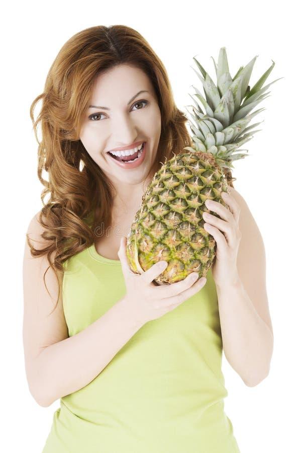 Mujer feliz con la fruta fresca de la piña fotos de archivo libres de regalías